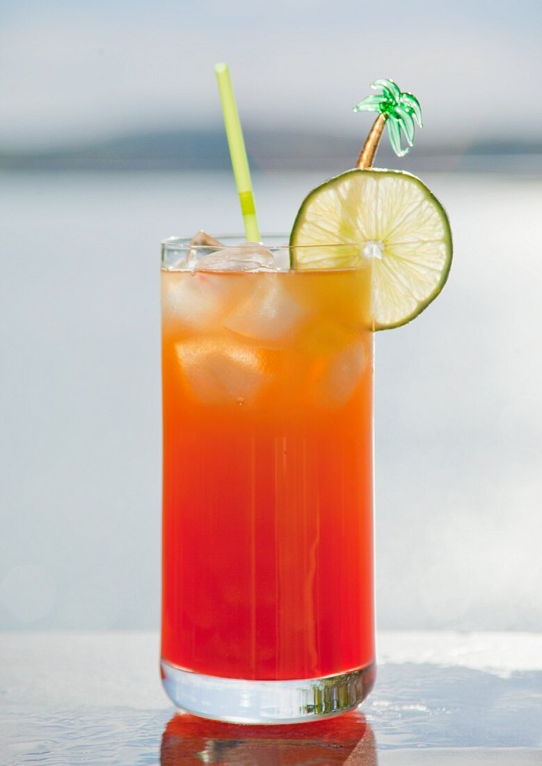 A Mai Tai cocktail on a table by a lake