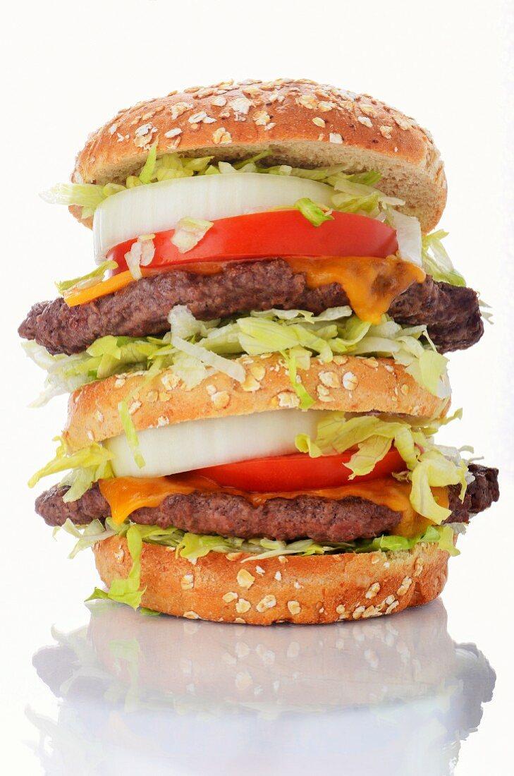 A double decker cheeseburger on a white surface