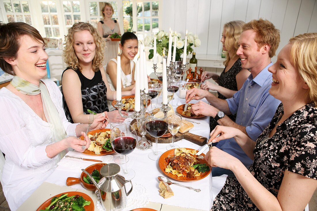 Friends having pasta, vegetables and red wine for lunch