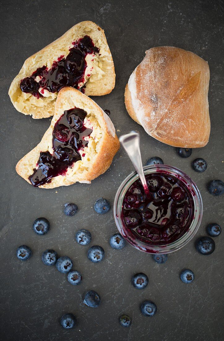 A jar of jam with blueberries and bread rolls