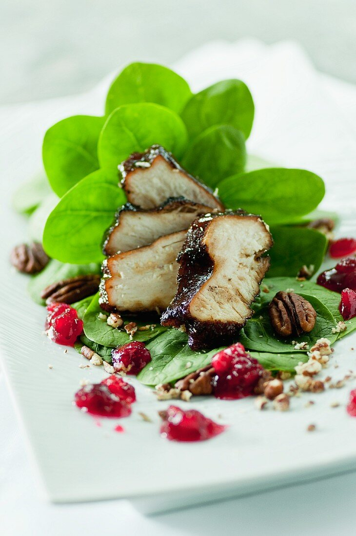 A salad with baby spinach, red-wine chicken, lingonberries and roasted pecan nuts