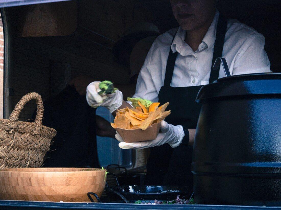 Street food – a vendors handing over a bowl of nachos