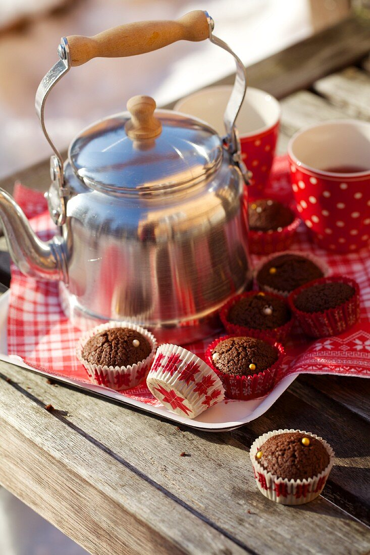 Mini chocolate muffins with a tea can and cups on a tray