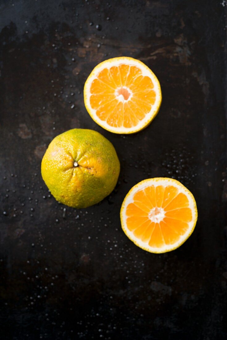 Ugli fruit, whole and halved, on a black surface