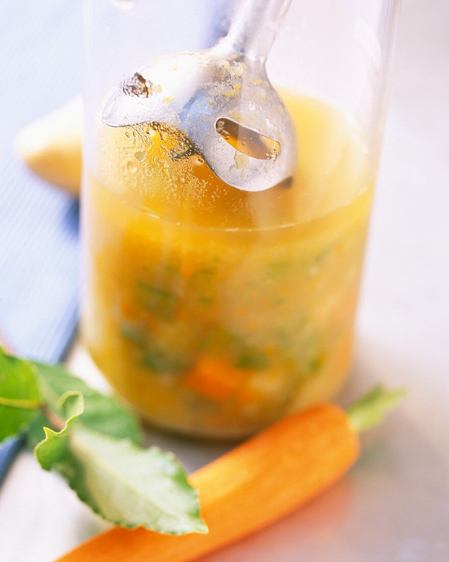 Vegetable soup to being puréed in a mixing cup