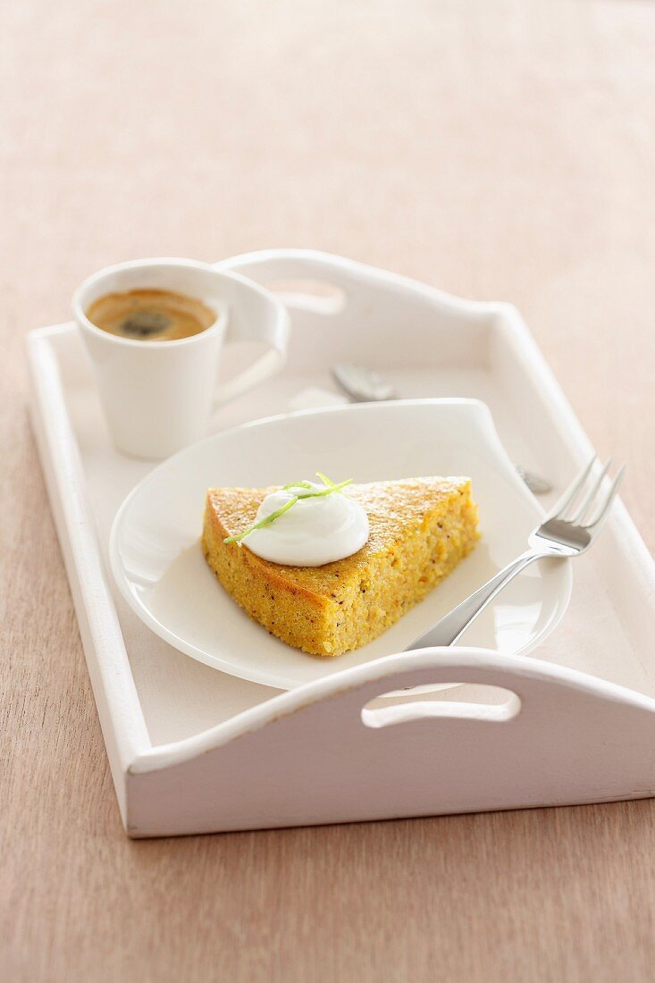 A slice of almond tart with cream and coffee