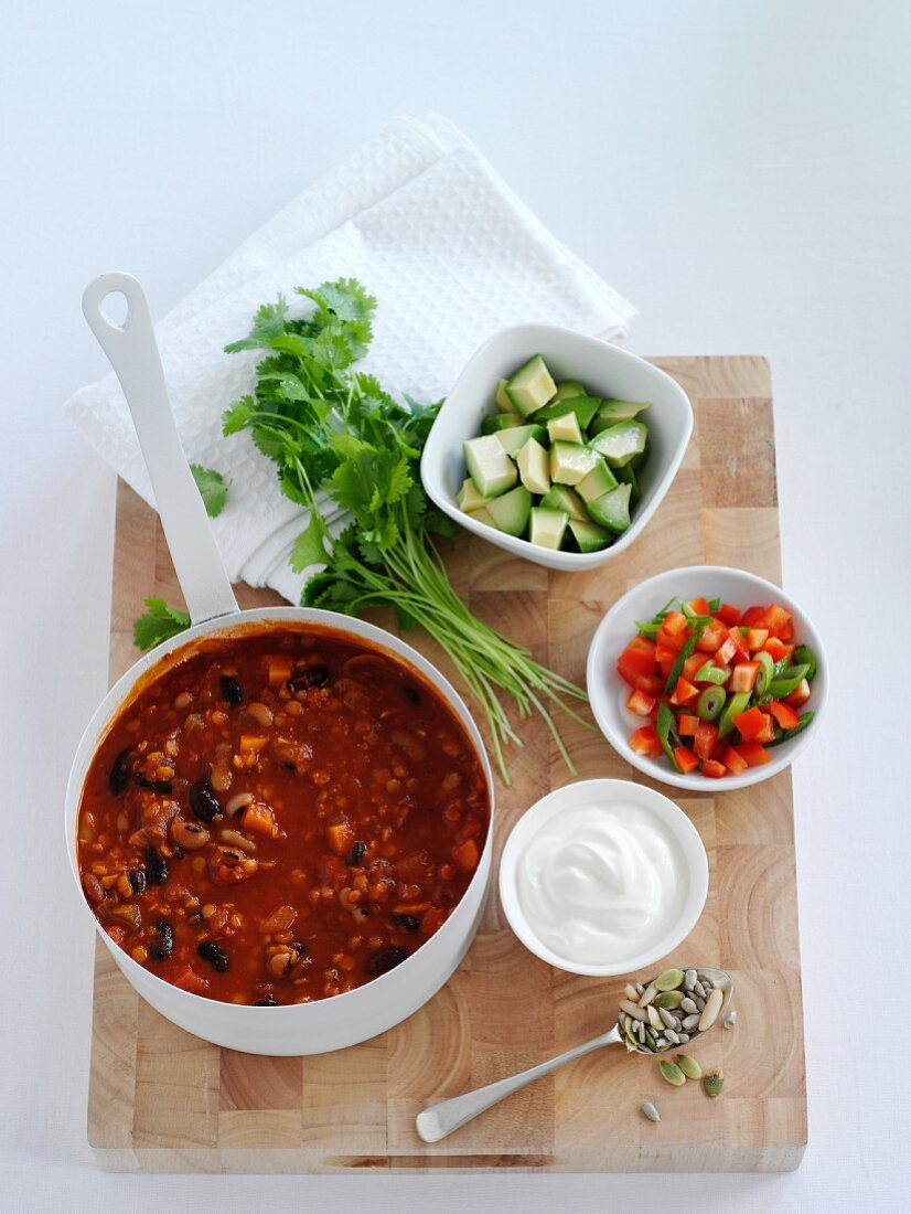 Bean soup with ingredients for seasoning on a wooden board