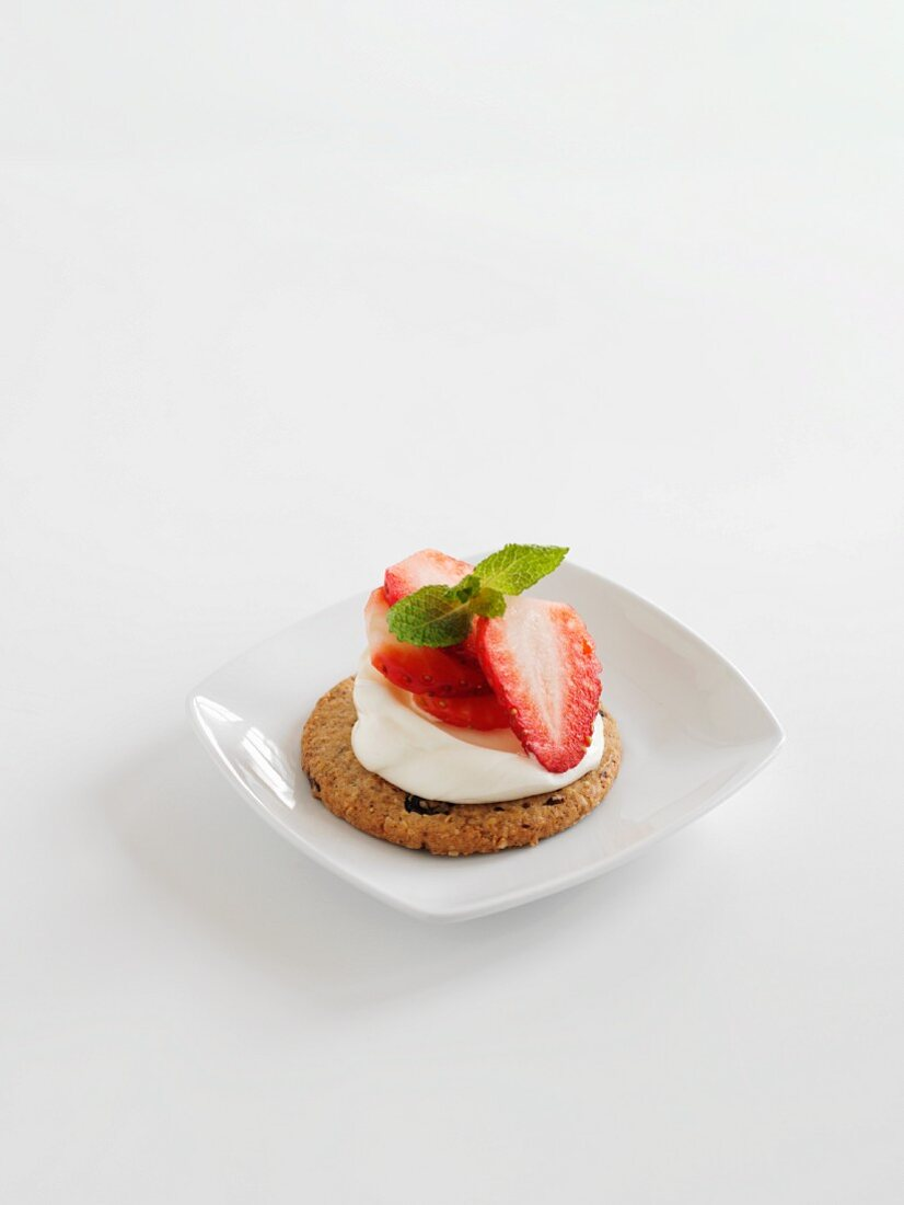 An oat cake topped with strawberries and cream on a white surface