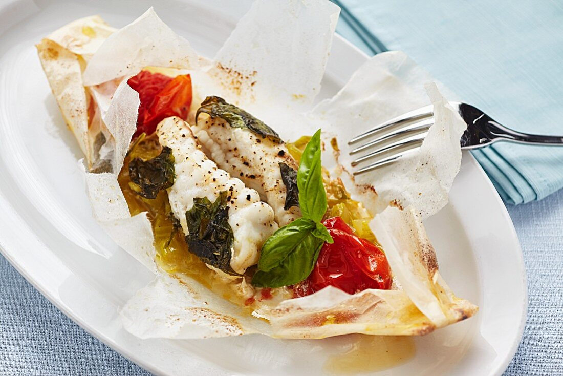 Cod cooked in parchment paper with tomatoes and herbs