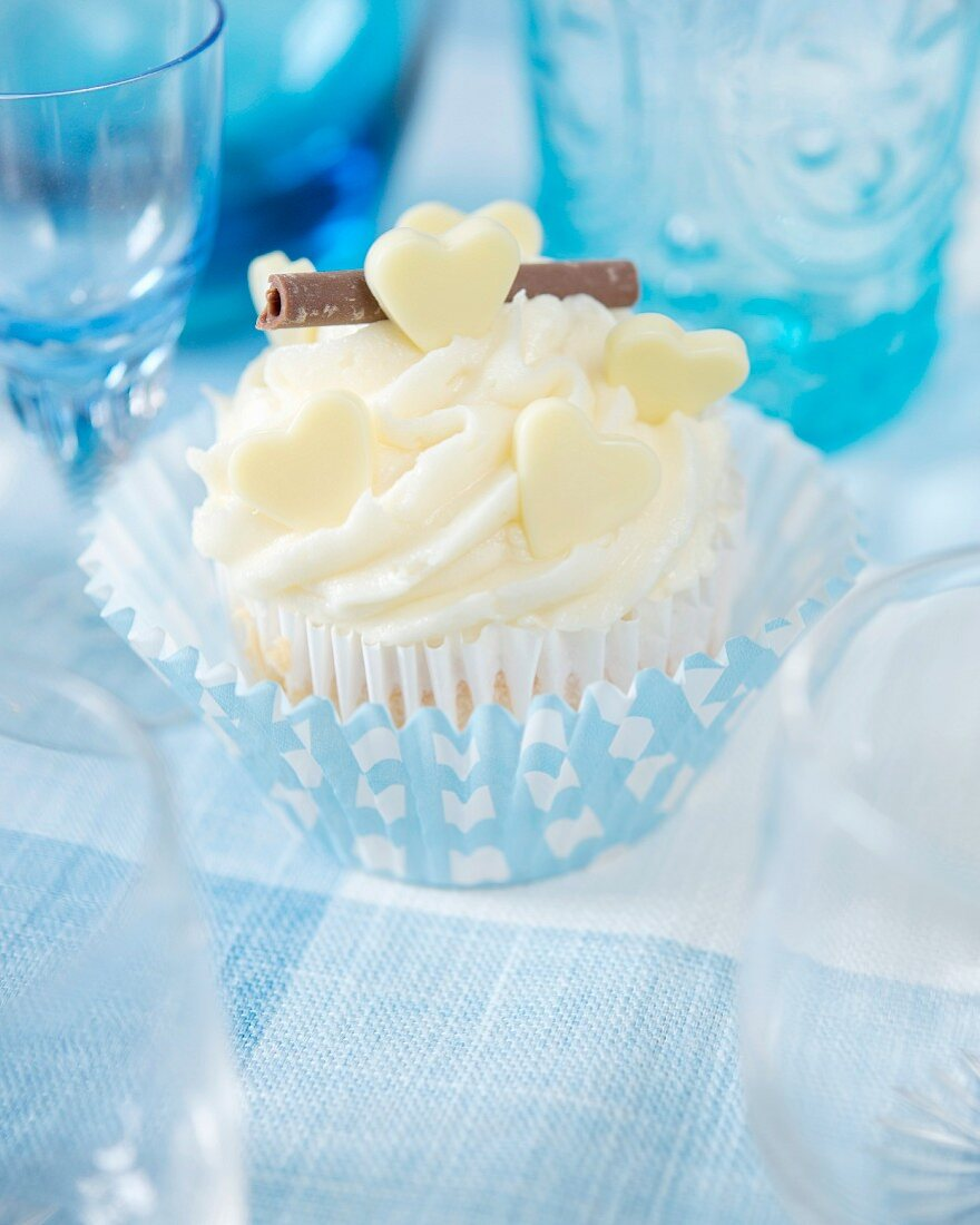 A white chocolate cupcake decorated with white chocolate hearts