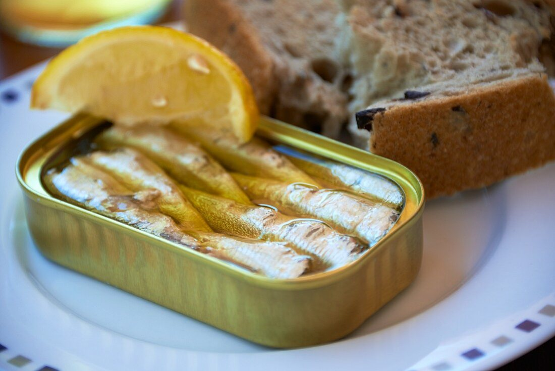 A tin of sardines with a lemon wedge and bread