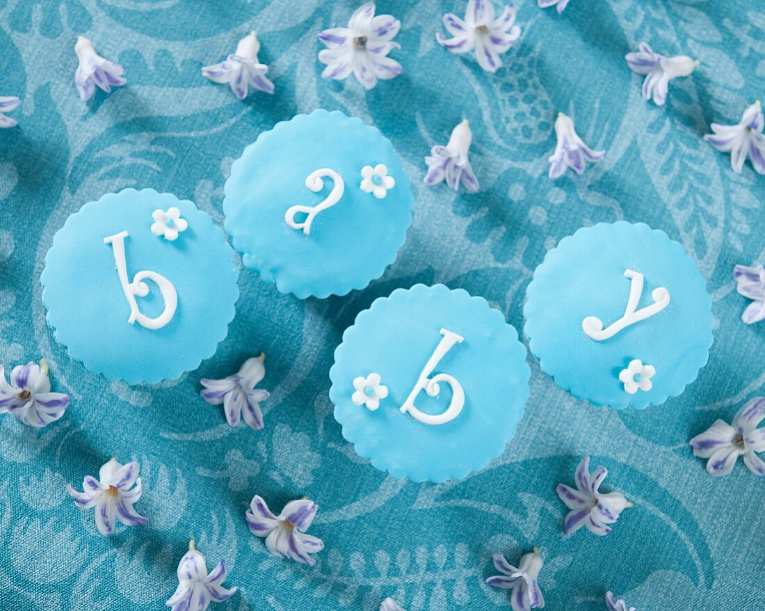 Four pastel-blue cupcakes spelling the word 'baby'