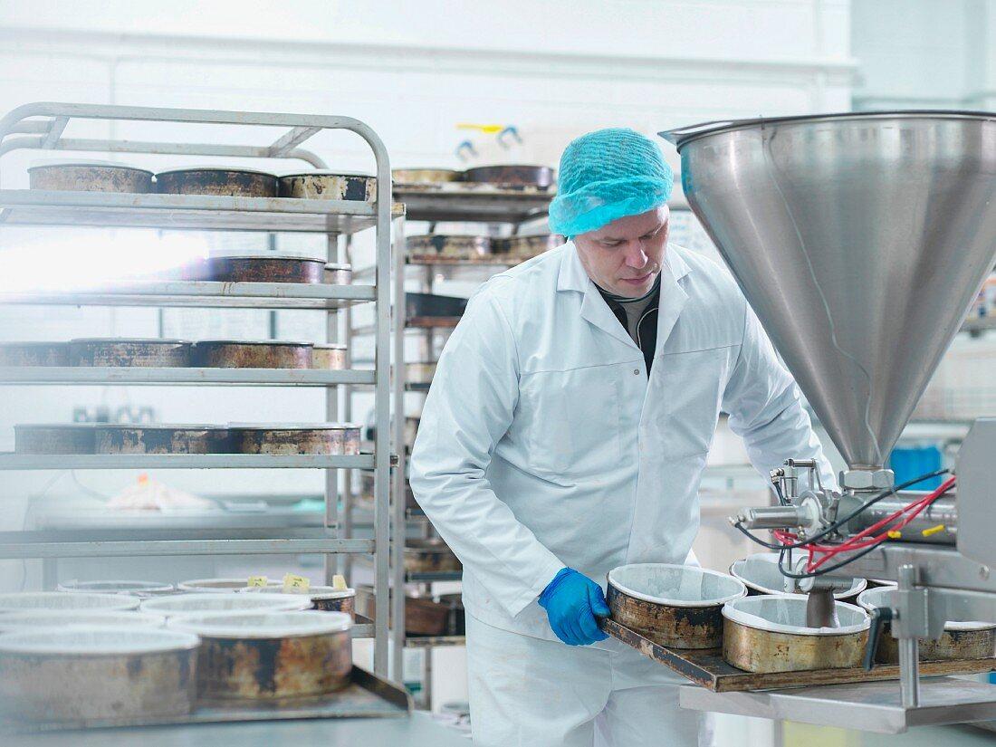 Arbeiter giesst Kuchenteig in Backformen in einer Kuchenfabrik