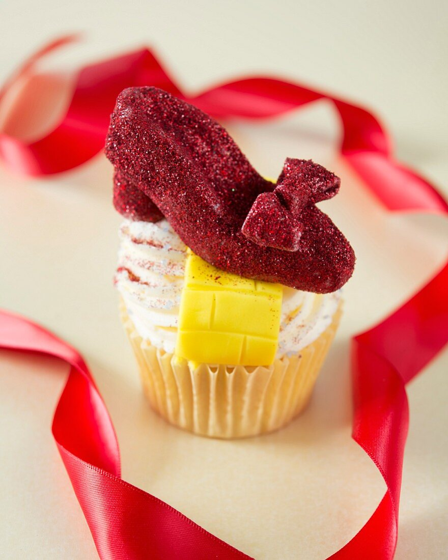 A Wizard of Oz themed cupcake decorated with a red shoe and a yellow brick road