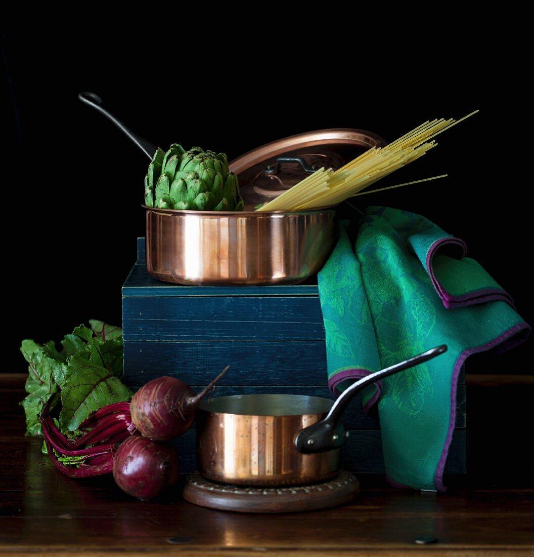 An arrangement of copper pans, vegetables and pasta