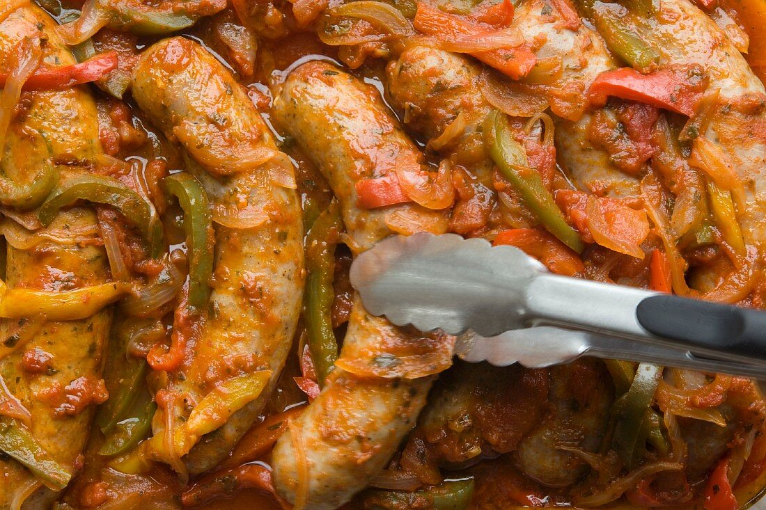 Baked sausages with peppers and onions (full frame)