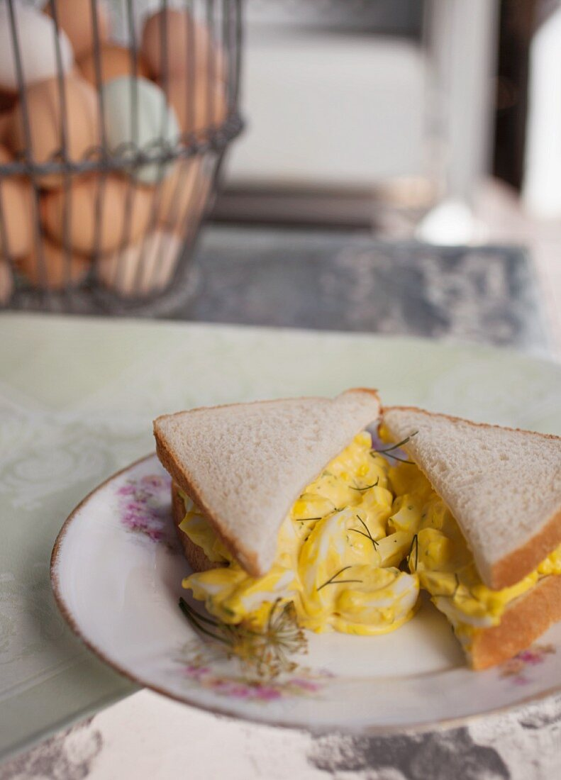 A halved egg salad sandwich with dill