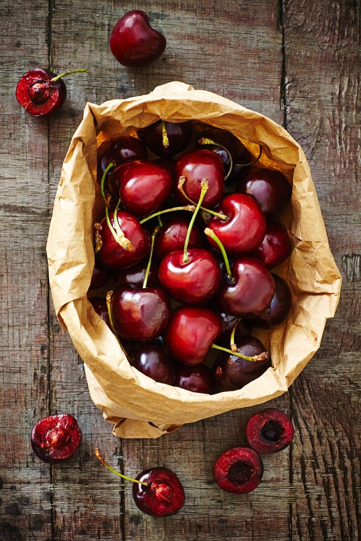 Fresh Spanish cherries in a brown paper bag on a wooden board