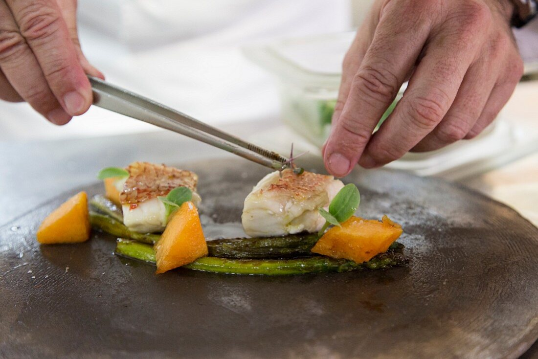 Fish fillets on green asparagus with melon