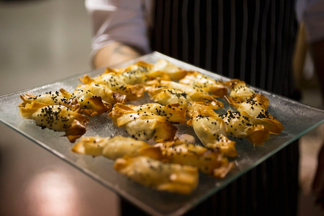 A person holding filo pastries on a glass platter