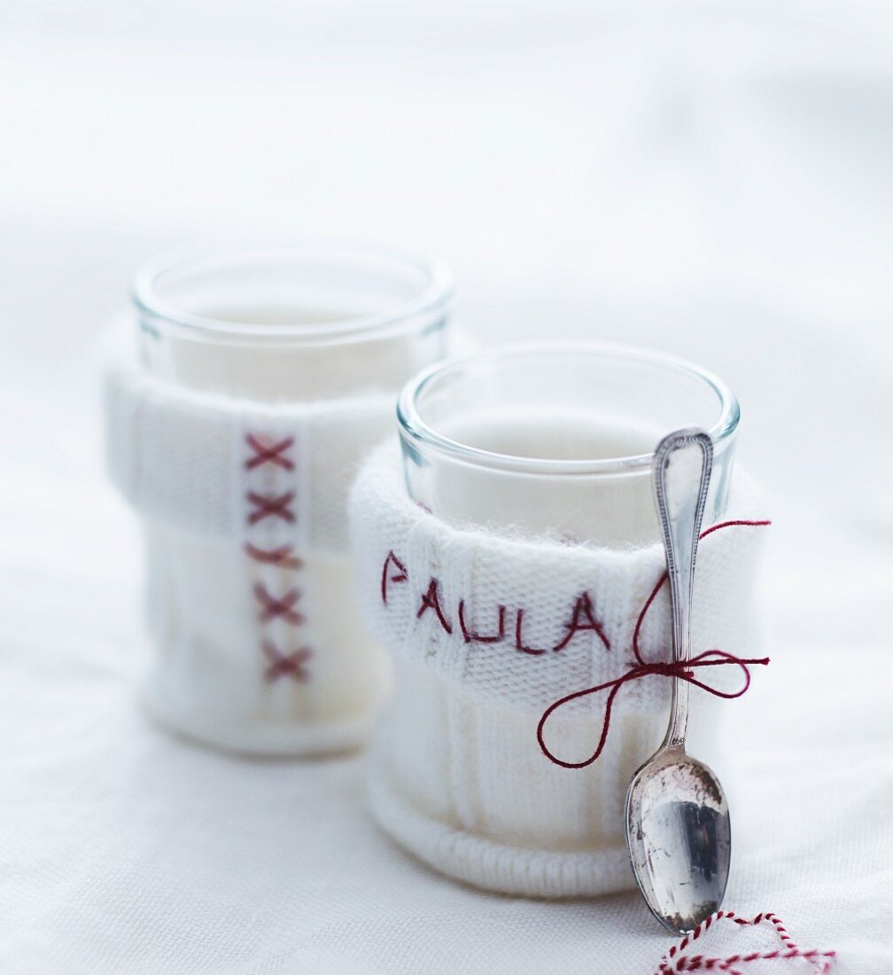 White knitted teacup cosies embroidered with pattern of crosses and name
