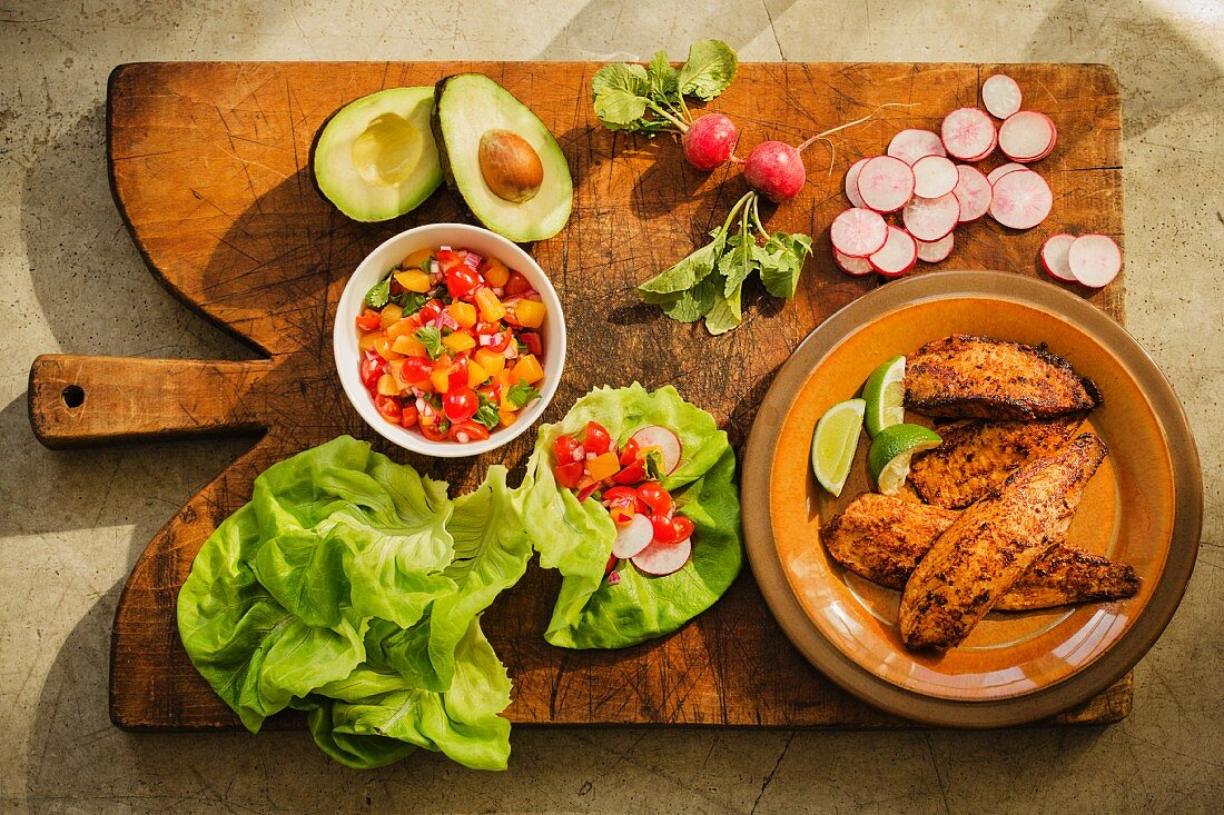Ingredients for tilapia wrapped in lettuce with a peach and tomato salsa (seen from above)