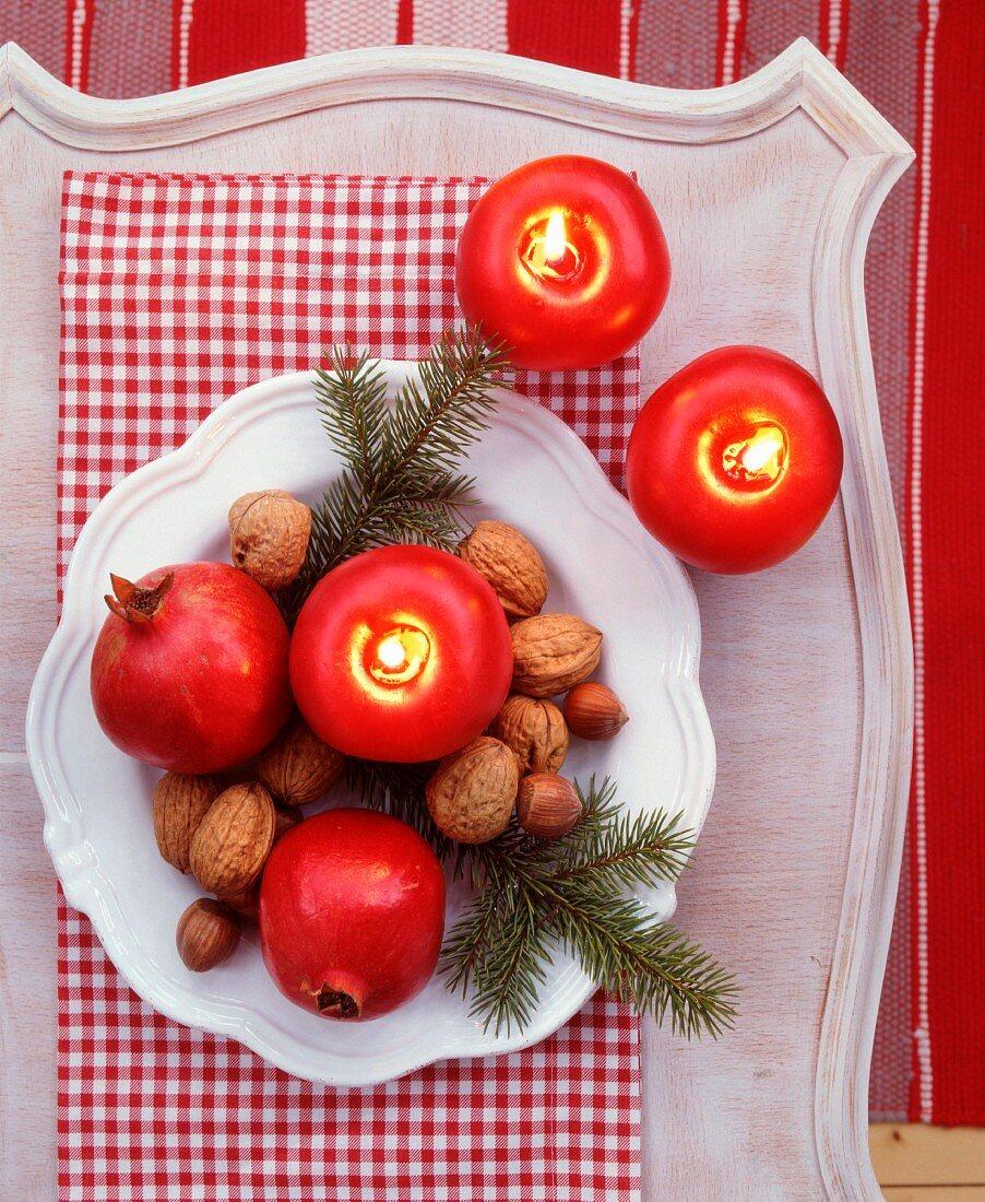 Teller mit Tannengrün, Nüssen, Granatäpfeln und apfelförmigen Kerzen