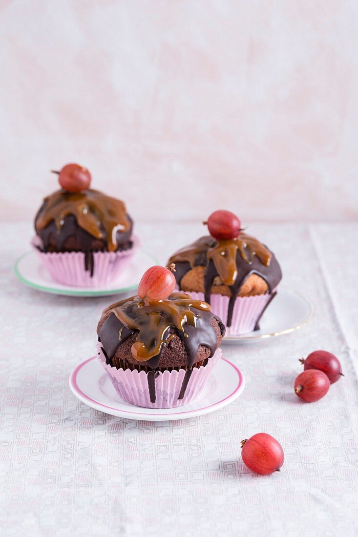 Muffins with chocolate glaze, caramel sauce and gooseberries