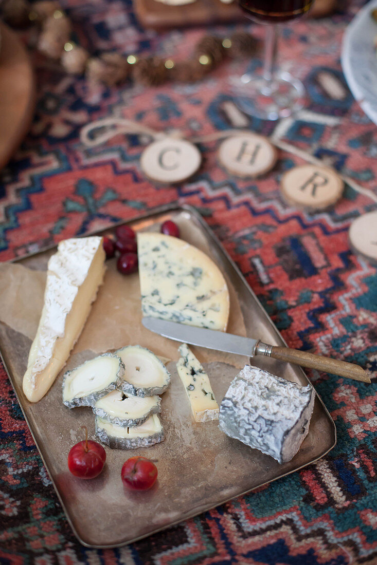 A cheese platter for a picnic-style Christmas meal on a kilim rug