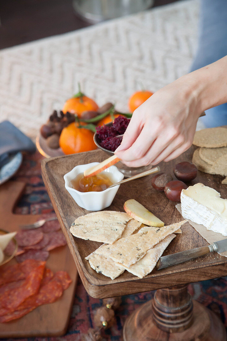 A cheese platter with chutney and crackers for a picnic-style Christmas meal