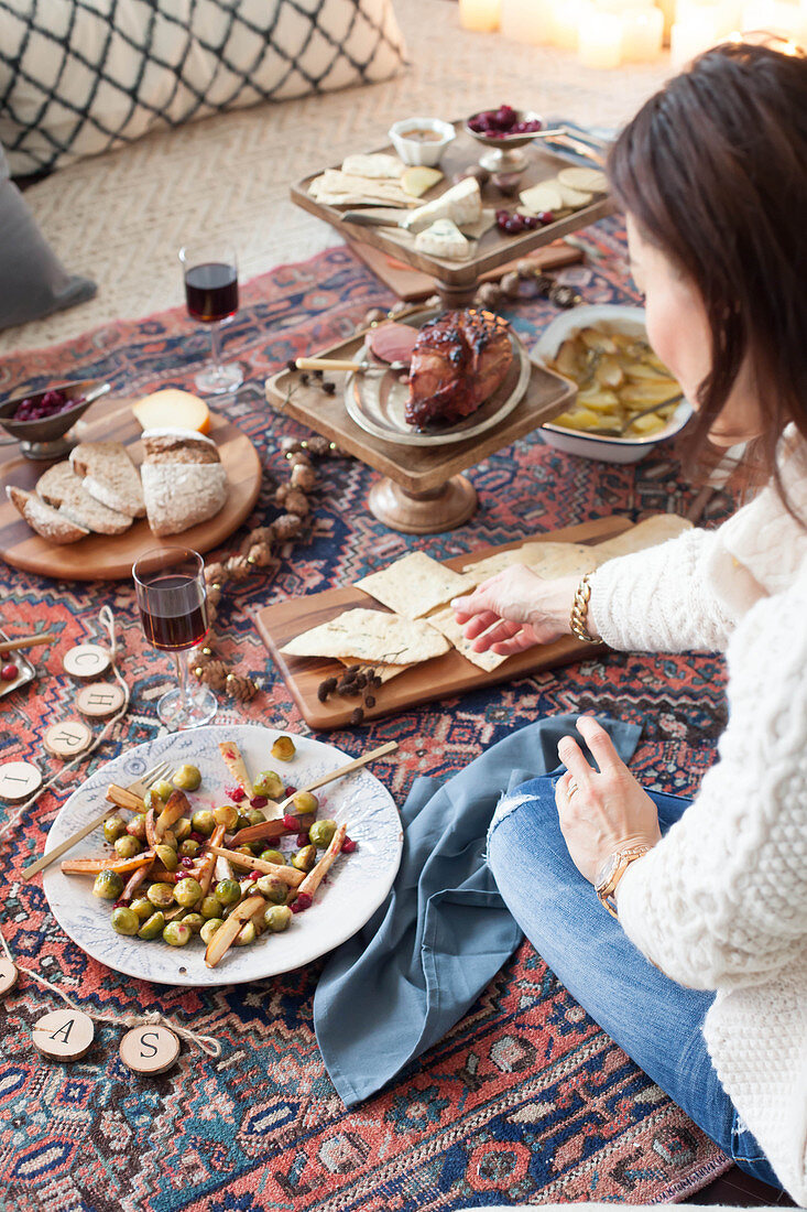 A picnic-style Christmas meal on a kilim rug with a cheese platter, salad and roast ham
