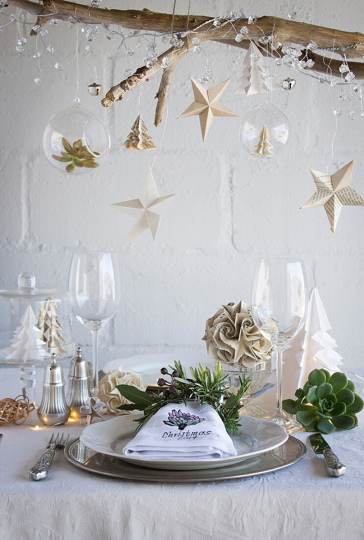 A table decorated for Christmas with paper decorations and a napkin ring of herbs
