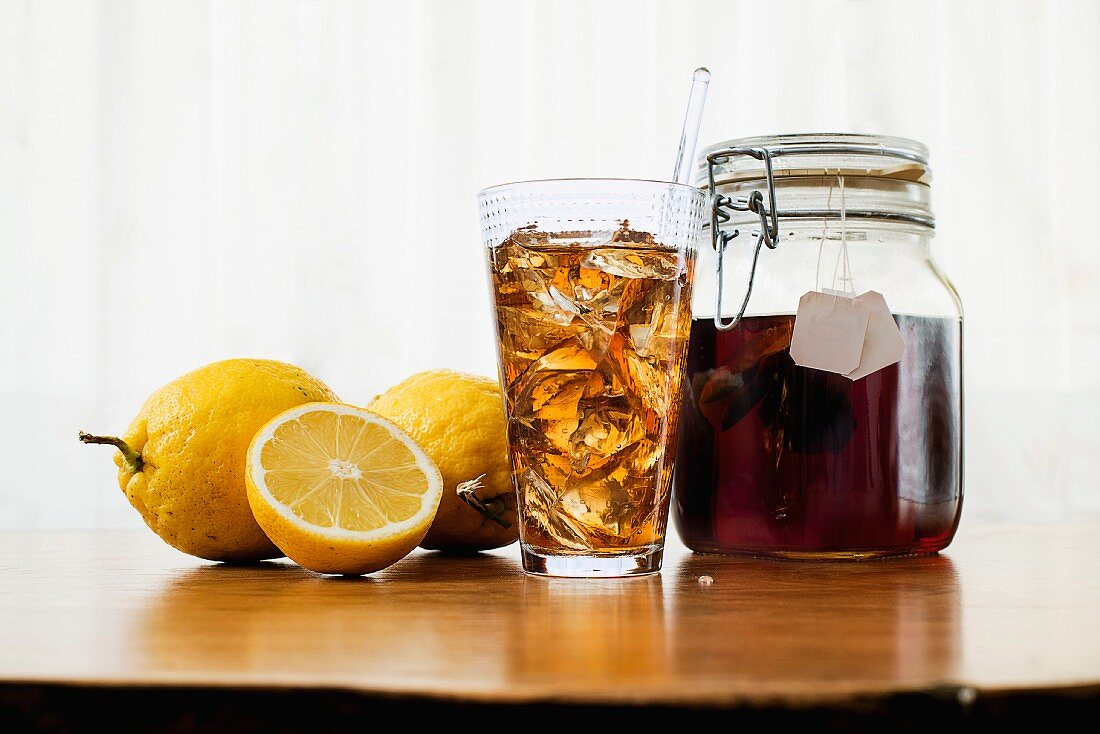 Iced tea in a glass and a flip-top jar next to lemons