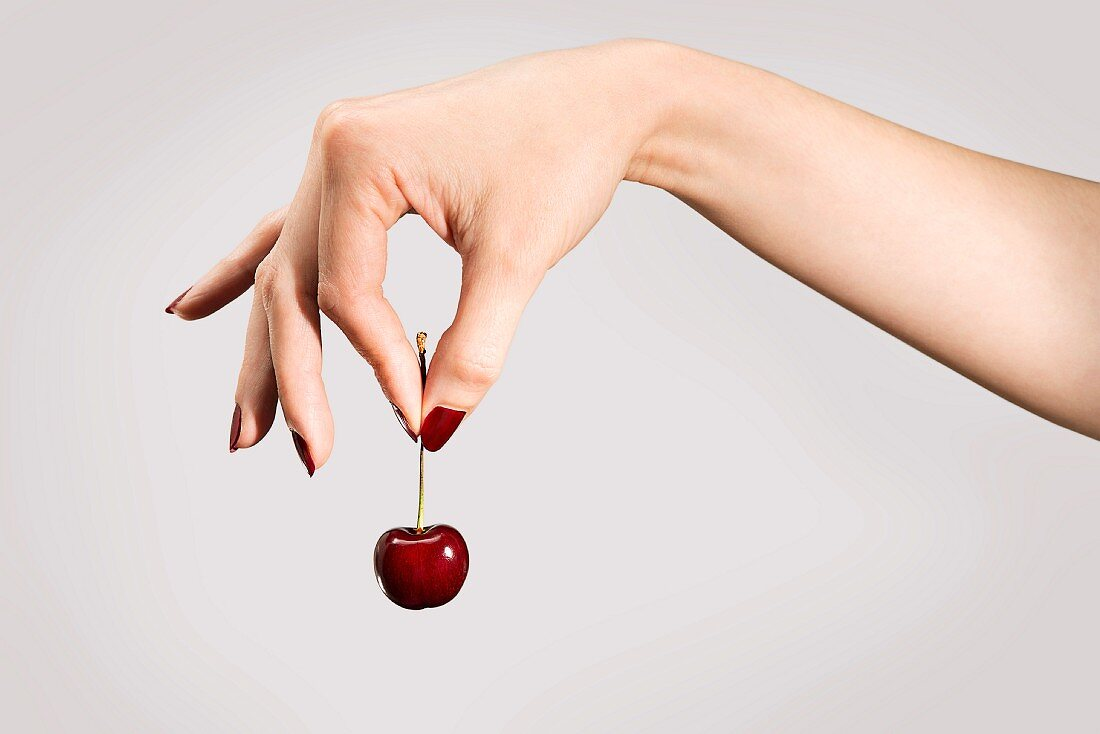 A woman's hand holding a cherry by the stem between her thumb and forefinger