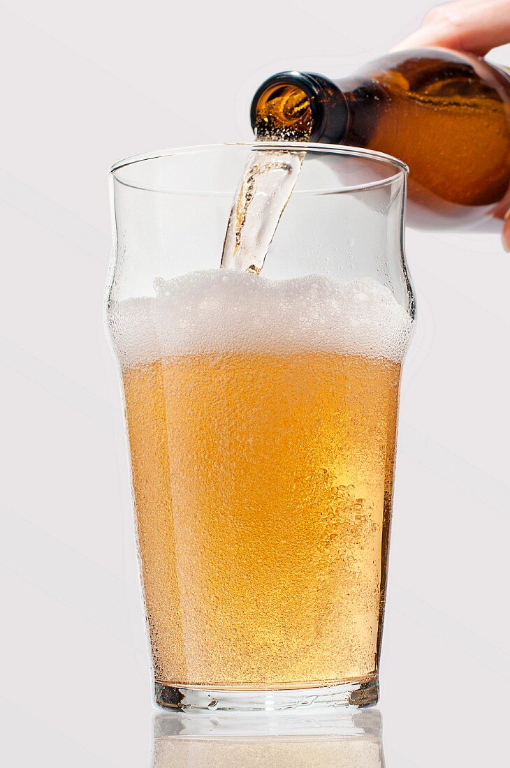 Lager being poured from a bottle into a glass