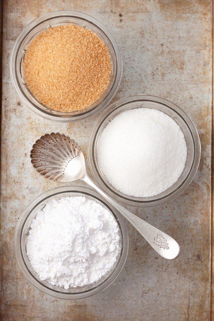 Various types of sugar in glass bowls: white sugar, brown sugar and icing sugar