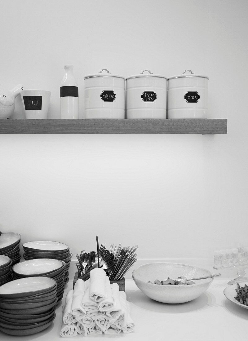 A stack of plates next rolled up napkins on a buffet below a shelf of storage containers