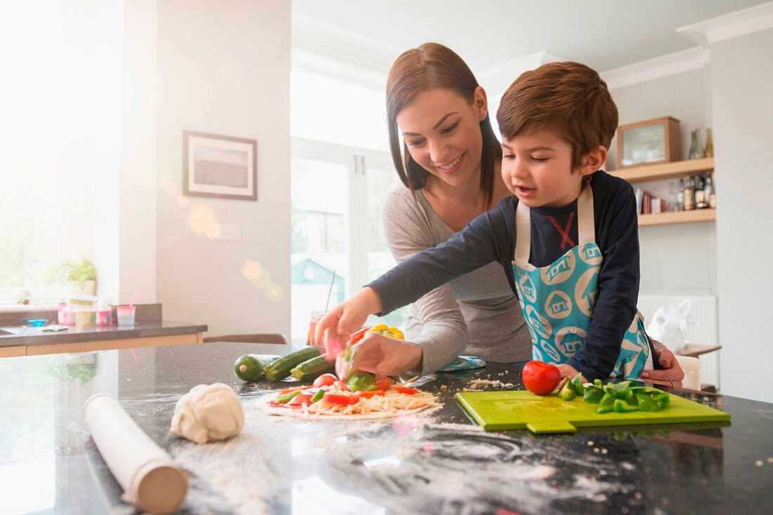 A mother and son preparing pizza together in a kitchen