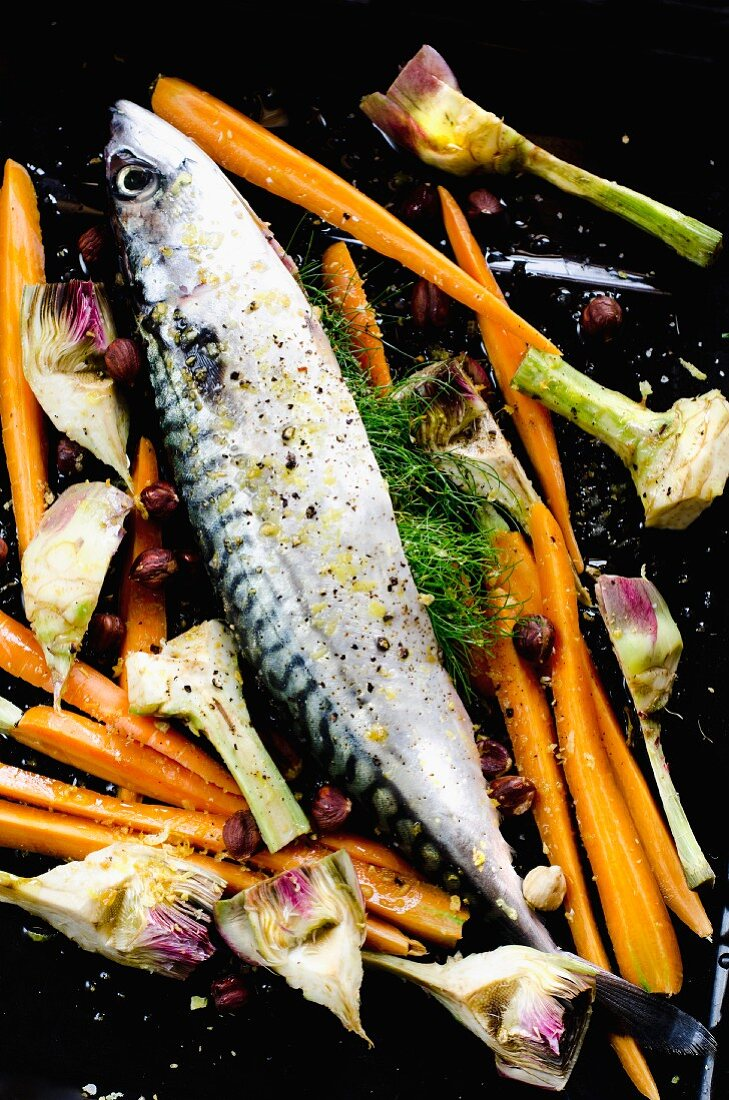 Mackerel with carrots and artichokes on a baking tray