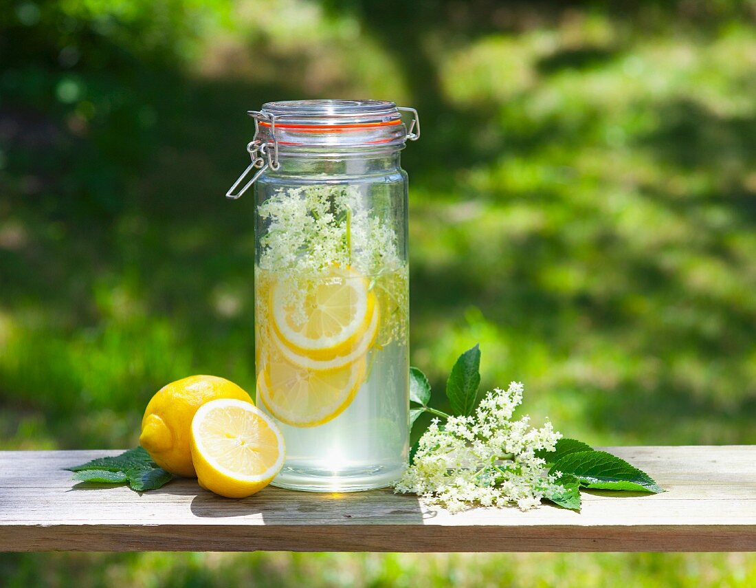 Homemade elderflower syrup with lemons on a table outside