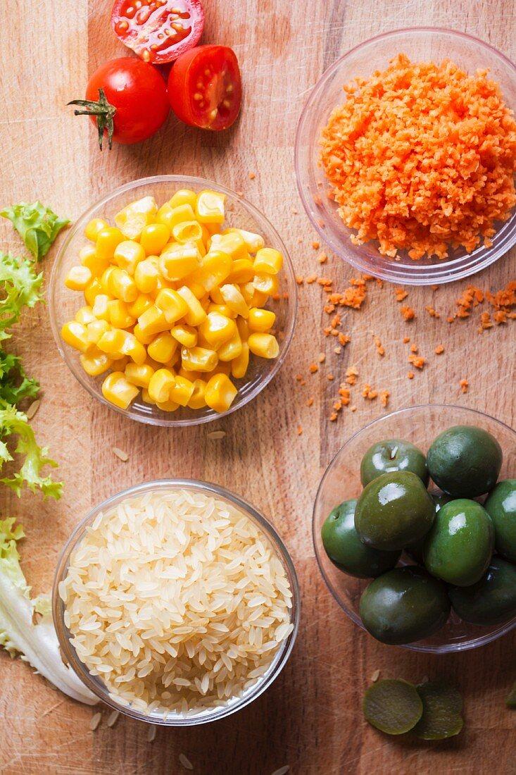 Zutaten für einen Reissalat mit Mais, grünen Oliven, Tomaten und Möhren