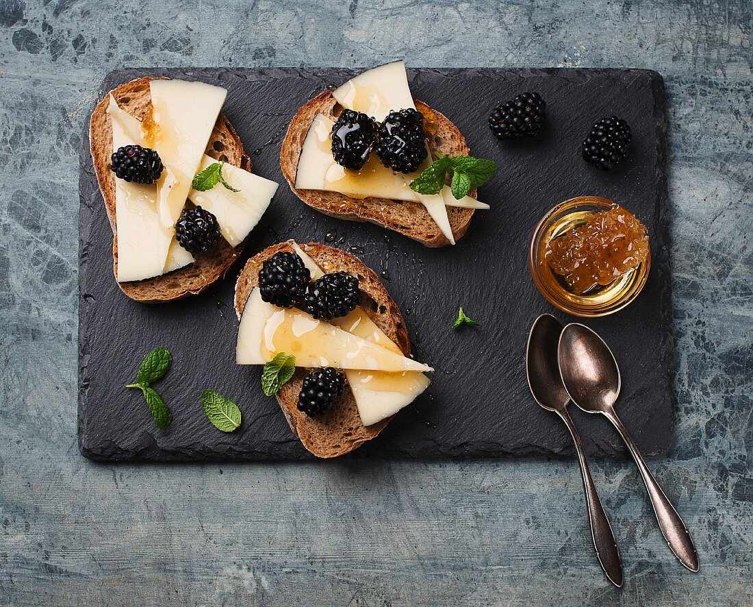 Bruschetta topped with cheese and blackberries