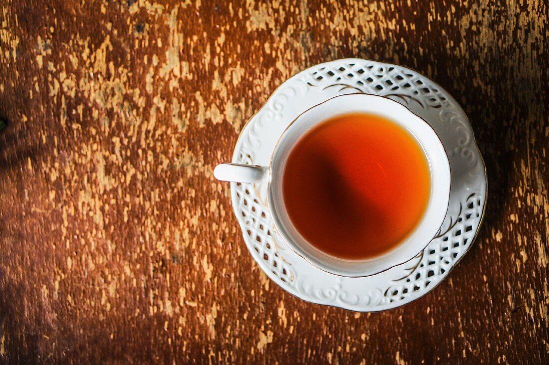 Eine Tasse Tee auf Holzuntergrund (Draufsicht)
