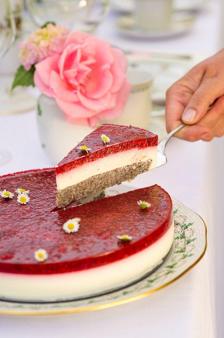 Himbeer-Joghurt-Torte mit Gänseblümchen, ein Stück auf Tortenheber