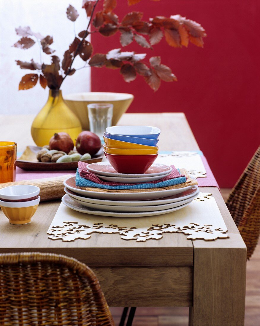 Colourful crockery and place mats hand-made from wooden veneer on rustic wooden table