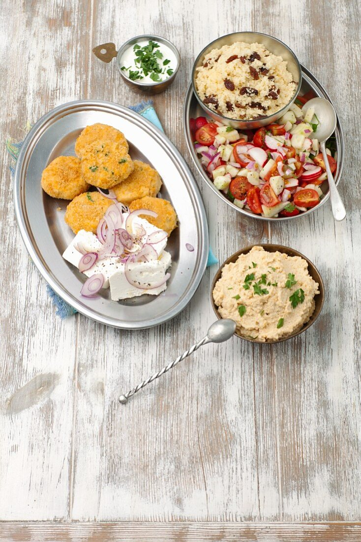 Falafel with feta cheese, couscous with a tomato and cucumber salad, and hummus