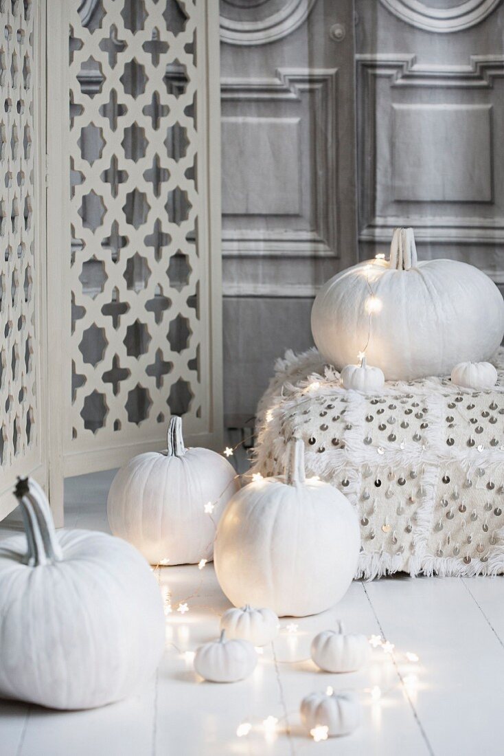 Halloween arrangement of white-painted pumpkins, fairy lights and floor cushions