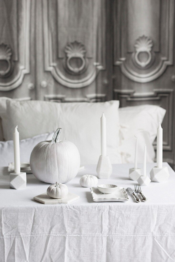 Halloween arrangement of white pumpkins and candles on table