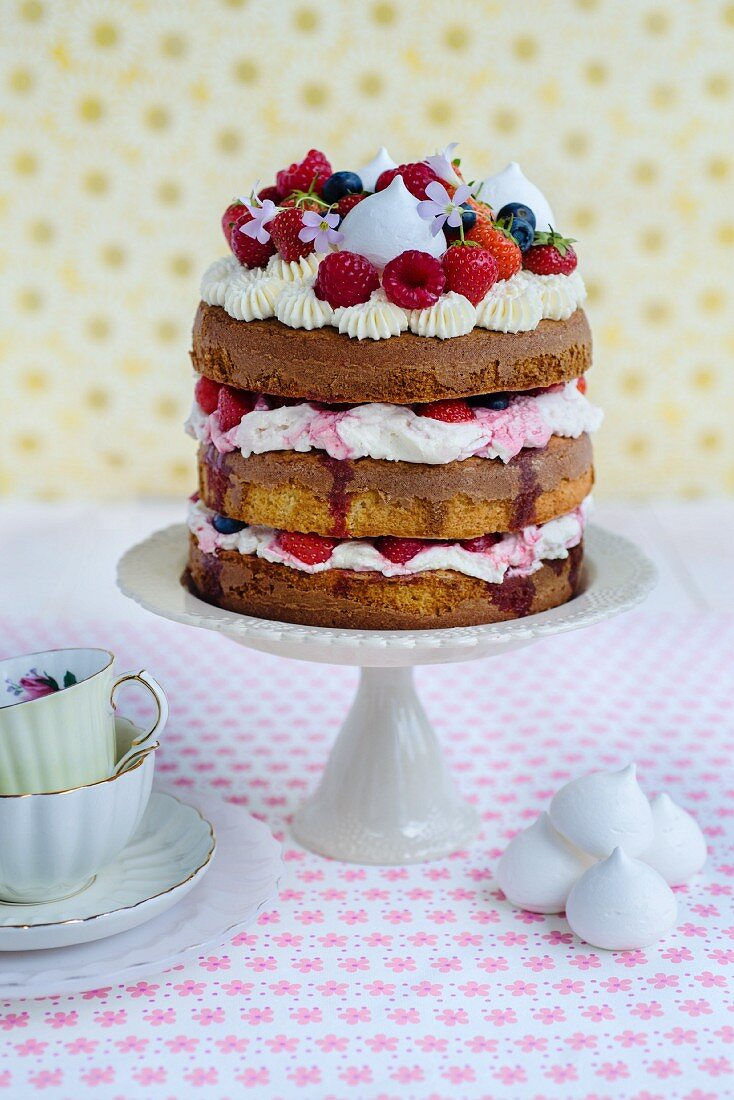 An Eton Mess layer cake with strawberries, raspberries and blueberries on a cake stand