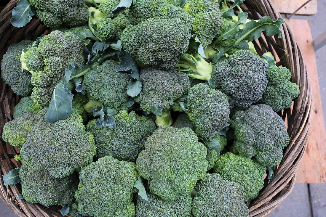 Organic green broccoli in a wicker basket at a market